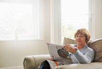 Senior woman sitting in armchair reading magazine — Stock Photo