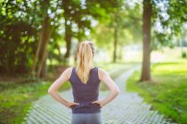 Young girl, outdoors, hands on hips, preparing herself for run — Stock Photo