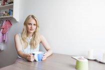 Portrait de jeune femme aux longs cheveux blonds boire du café dans la cuisine — Photo de stock