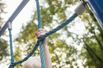 Baby girl on climbing frame at park, focus on hand — Stock Photo