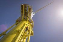 Инженер скалолазание ветрогенератор с лодки на оффшорной ветроэлектростанции, вид с низкого угла — стоковое фото