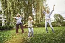 Membros fêmeas da família que jogam com aros do hula — Fotografia de Stock