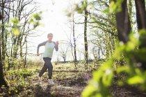 Donna anziana sportiva che corre nella foresta — Foto stock