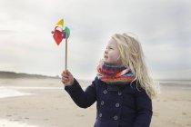 Retrato de menina de três anos com moinho de vento de papel na praia, Bloemendaal aan Zee, Países Baixos — Fotografia de Stock