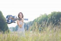 Portrait de femme adulte milieu et se promener dans le champ avec guitare acoustique — Photo de stock