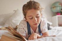 Девочка лежит на кровати чтение книги — стоковое фото
