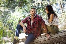 Giovane coppia seduta su un albero nella foresta — Foto stock