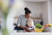 Mère, aider les fils à préparer de la nourriture dans la cuisine — Photo de stock