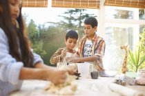 Children making dough in kitchen at home — Stock Photo