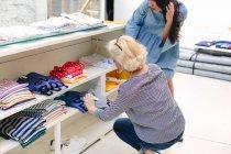 Женщины в магазине одежду, смотрит на цену на футболках — стоковое фото