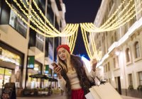 Young female shopper reading smartphone texts on street at xmas, London, UK — Stock Photo