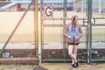 Молодая женщина стоит рядом со спортивной площадкой, Лондон, Великобритания — стоковое фото