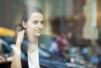 Молодая деловая женщина, выглядывающая из окна кафе, Лондон, Великобритания — стоковое фото