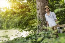 Young man leaning against tree with watering can — Stock Photo