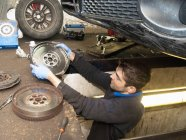 Mechanic checking discs of wheel underneath car — Stock Photo