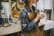 Jovem artesã bebendo café em oficina de órgão de tubulação — Fotografia de Stock
