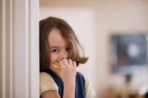 Fille manger sandwich et regarder la caméra — Photo de stock