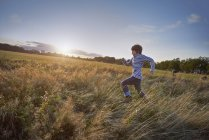 Boy running out in park meadow, side view — Stock Photo