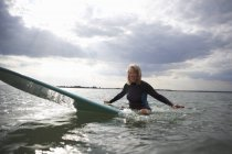 Portrait of senior woman sitting on surfboard in sea, smiling — Stock Photo