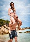 MID дорослий чоловік дає подруги плеча їздити на пляжі, Ла-Маддалена, Сардинія, Італія — стокове фото