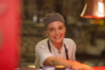 Портрет молодої жінки шеф-кухар виступає позабіржовому кафе — стокове фото