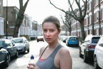 Portrait de jeune coureuse dans l'eau potable de la rue — Photo de stock