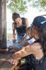 Молодая женщина и подростки смотрят на карту и строят планы — стоковое фото