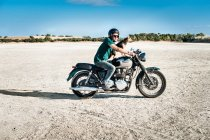 Mid adult man and dog riding motorcycle on arid plain, Cagliari, Sardinia, Italy — Stock Photo