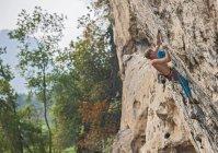 Maschio alpinista arrampicata a montagna bianca - una scogliera di calcare a Yangshuo, Guangxi Zhuang, Cina — Foto stock