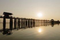 Силуэт Пирс с отражением в воде в яркой подсветкой — стоковое фото