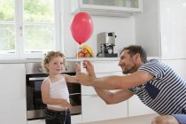 Girl holding balloon with father in kitchen — Stock Photo