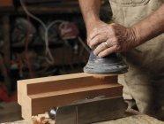Abgeschnittenes Bild des Bootsbauers, der in der Werkstatt Holz schleift — Stockfoto