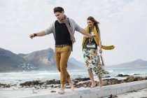 Young couple walking along cement block on beach, Cape Town, Western Cape, South Africa — Stock Photo