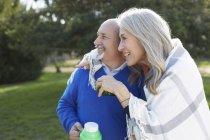 Пара, завернутая в одеяло, держащая напитки, фляжка, глядя в сторону, улыбаясь — стоковое фото
