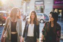 Троє молодих жінок прогулюються по міській вулиці — стокове фото