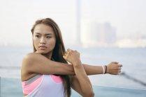 Junge Frau, die Ausübung der Arme und Schulter am Wasser, Hong Kong — Stockfoto