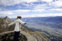 Young woman with arms open on top of mountain, Innsbruck Tyrol, Austria — Stock Photo