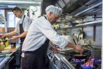 Шеф-повара готовят блюда в традиционной итальянской кухне ресторана — стоковое фото