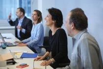 Uomini d'affari seduti alla scrivania in ufficio interno — Foto stock