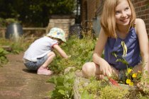 Two sisters digging in garden grass and soil — Stock Photo