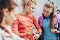Three female runners checking time on smartwatch — Stock Photo