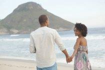 Couple strolling hand in hand on beach, Rio De Janeiro, Brazil — Stock Photo