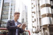 Businessman using digital tablet in street, London, UK — Stock Photo