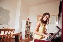 Junge Frau sitzt spielen Klavier im Speisesaal — Stockfoto