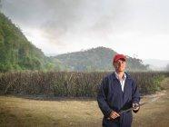 Trabalhador com facão e cana de açúcar queimada — Fotografia de Stock