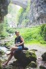 Donna che si siede sulla roccia nel flusso, colline di roccia e Ponte di pietra in fondo, Garda, Italia — Foto stock