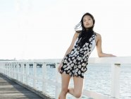 Portrait of young woman leaning against pier railings, Port Melbourne, Melbourne, Victoria, Australia — Stock Photo