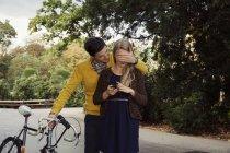 Giovane uomo copertura fidanzata occhi nel parco — Foto stock