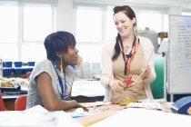 Docente donna che chiacchiera con lo studente in classe tessile — Foto stock