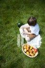 Накладные зрения мальчика крест ноги на траве заливки молока в стаканы — стоковое фото